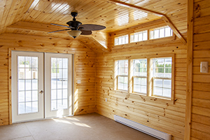 Custom Home Office Building from Pine Creek Structures | Finished Shed Interior with knotty pine walls, heat, fan, and custom upgrades