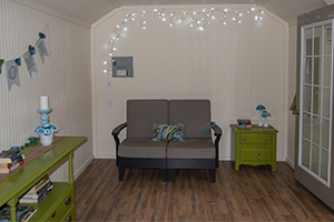 Custom Home Office Building from Pine Creek Structures | Finished Shed Interior with painted beadboard walls, electrical package, other custom upgrades, and decorations