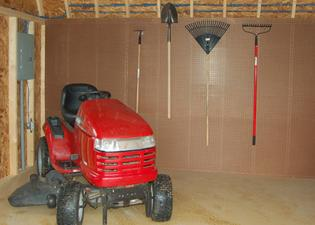 Storing a riding lawn mower and other lawn care tools inside a shed