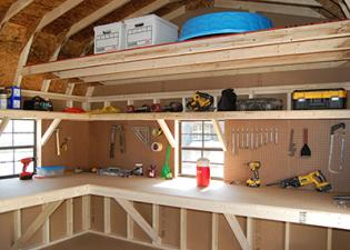 Storing a items in a shed with a loft, shelves, a workbench, and pegboard