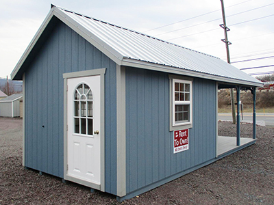 custom cape cod style building with porch and sliding patio doors from pine creek structures