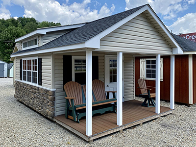 custom cape cod style building with cape dormer, stonework, and porch from pine creek structures