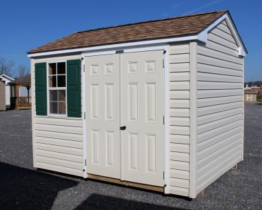 Pine Creek 8x10 HD Vinyl Peak with Sand walls, White trim, Green shutters, and Shakewood shingles